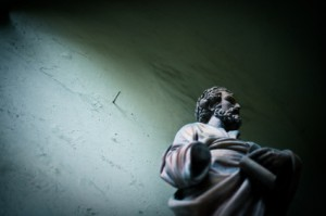 Old, damaged statue of St. John the Baptist (S. Giovanni Battista) in an inner court of an ancient building in Italy.